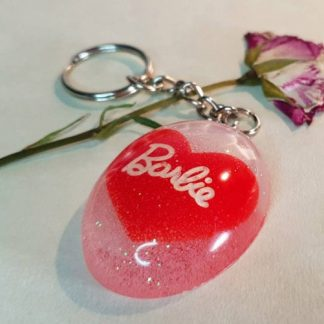 A red heart-shaped keychain with a Barbie theme which has been handmade from epoxy resin by The Pea Hive