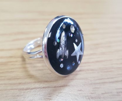 A black ring made form epoxy which is adjustable and features a star and rocket as part of a space theme