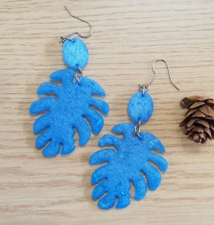 A set of leaf-shaped dangle drop earrings which are blue in colour and handmade from epoxy resin by The Pea Hive