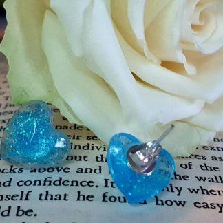 A set of blue millie heart stud earrings which have been handmade from epoxy resin by The Pea Hive