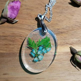 A pendant necklace handmade from epoxy resin and set with a real blue pressed flower makes for a cool piece of jewellery from The Pea Hive