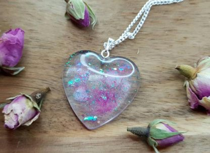 A clear heart-shaped pendant necklace set with glitter to create an unworldly looking piece of resin jewellery