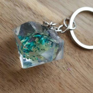 A diamond shaped keyring in blue which is set with dried flowers for a cute looking accessory
