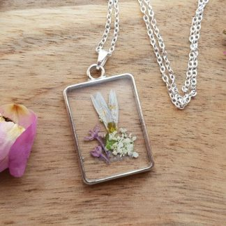 An elegant necklace pendant handmade from epoxy resin and set with garden flowers