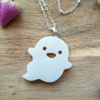 A spooky fun-loving ghost pendant made from epoxy resin and attached to a necklace by The Pea Hive