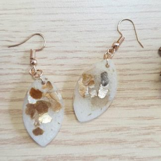 These natural looking golden leaf-shaped earrings contain mica mineral flakes and have been handmade from epoxy resin by The Pea Hive