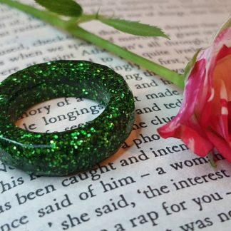 A green sparkle ring set with glitter which has been handmade from epoxy resin by The Pea Hive