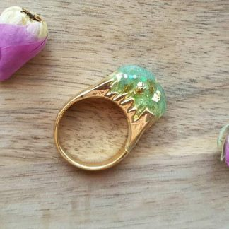 A fantasy ring with a green sparkle broken mountain set on top of a gold coloured band