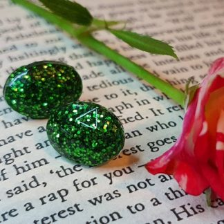 An oval-shaped set of stud earrings which are made from epoxy resin and set with glitter by The Pea Hive