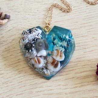 A geometric heart-shaped pendant necklace set with seashells, flowers and mica flake for a beach theme