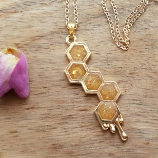 A pendant necklace handmade from epoxy resin by The Pea Hive which has been inspired by bees and honeycomb