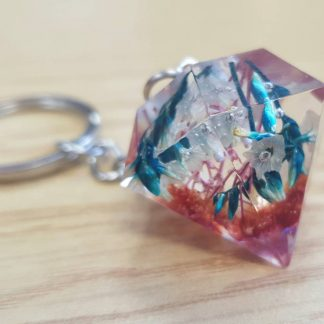 Pink and blue diamond-shaped keychain made from epoxy resin and set with dried flowers