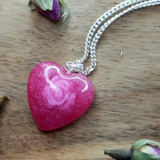 A vibrant pink heart-shaped necklace pendant which has been handmade from epoxy resin by The Pea Hive