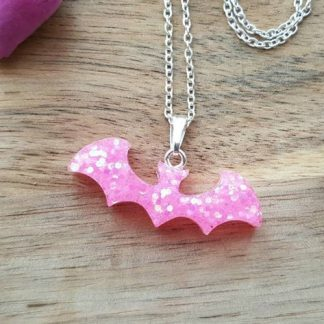 A pink bat pendant made from epoxy resin and sprinkled with glitter as part of a cool looking necklace made by The Pea Hive
