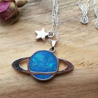 A pedant necklace made from epoxy resin featuring a blue planet and a silver star which has been handmade by The Pea Hive