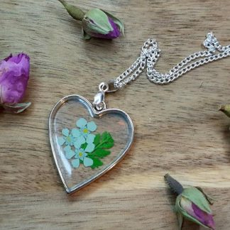 A heart-shaped pendant set with a real pressed blue flower makes for a fancy piece of resin jewellery