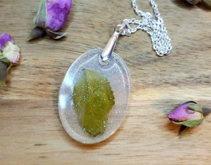 A pendant necklace handmade from epoxy resin with a real pressed rose leaf set inside