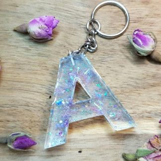 A sparkly letter keychain handmade from epoxy resin by The Pea Hive