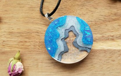A circular mermaid bubble seascape pendant handmade from epoxy resin by The Pea Hive