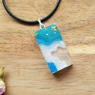 A rectangle pendant handmade from epoxy resin featuring a mermaid bubble seascape design attached to an adjustable faux leather necklace cord