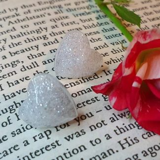 White heart-shaped stud earrings which have been handmade from epoxy resin by The Pea Hive