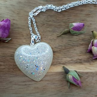 A heart-shaped pendant necklace made from epoxy resin by The Pea Hive which looks as though it could have been forged from stardust