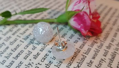 A set of round stud earrings which look like they have been made from white stardust rather than epoxy resin