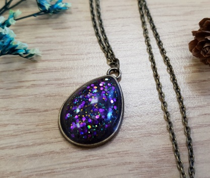 A teardrop-shaped purple sparkle necklace which is purple coloured and set with generous amounts of glitter
