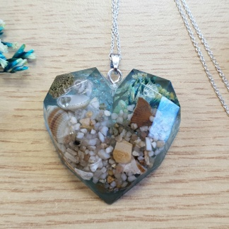 A heart-shaped pendant necklace made from epoxy resin and set with seashell, sand, glitter and mica flakes
