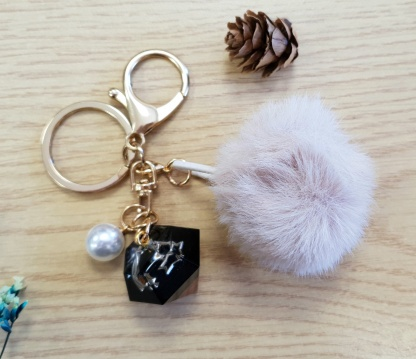 A diamond-shaped keychain charm set with a shooting star handmade from epoxy resin by The Pea Hive