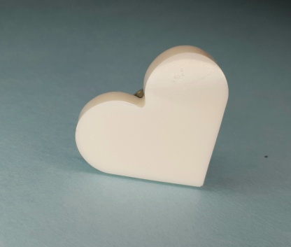 A fully adjustable White Heart Shaped ring which has been handmade from casting resin by The Pea Hive
