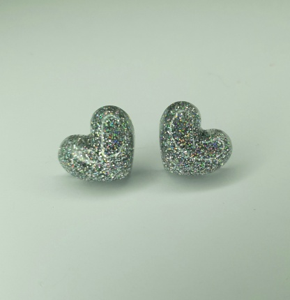 A set of holographic 3D heart shaped earrings handmade from casting resin
